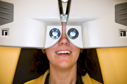 photo: woman having vision checked in automated Phoropter